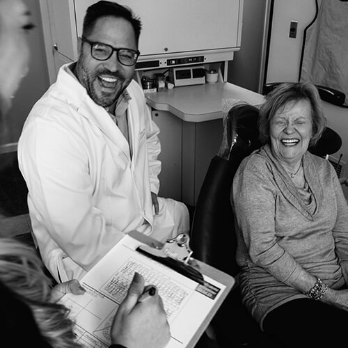 Shot of our Dentist in Pittston PA, laughing with an elderly patient