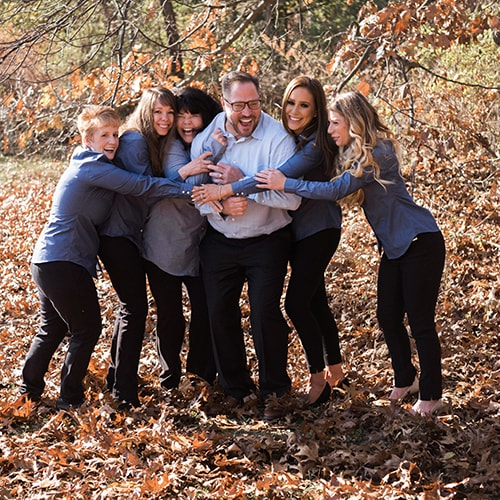 Dr. Salvatore Infantino and his friendly dental team laughing in the autumn leaves.