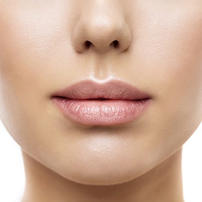 A woman with fuller lips and a wrinkle-free appearance, thanks to BOTOX and lip fillers