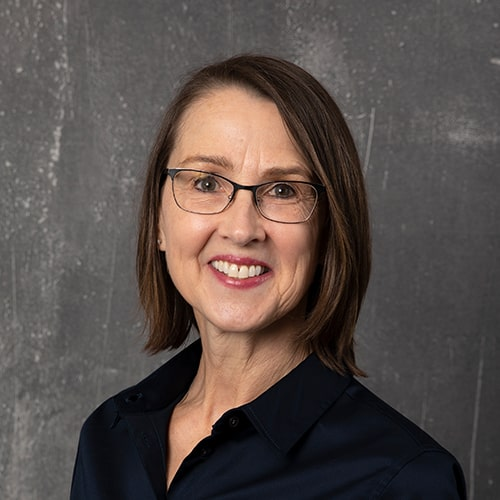 Patient Coordinator, Debbie, in a navy top and glasses on gray background