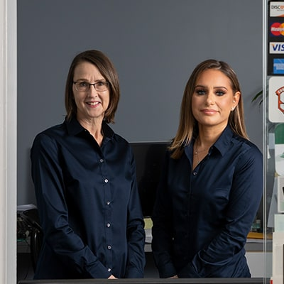 Debbie and Violet smiling - contact them to get all of your dental questions answered!